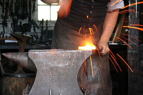 Photograph of a blacksmith hitting a bright, hot piece of metal on an anvil. The cooler sparks flying off are red hot. The metal itself is yellow hot.
