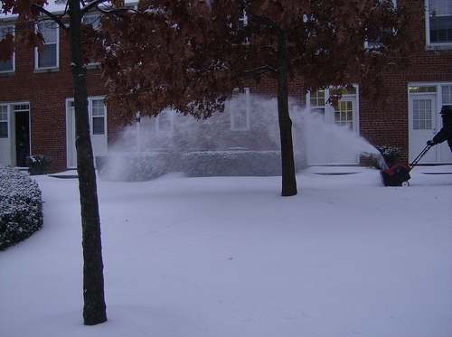 Photo of a snow covered area in front of a house where the snow appears dull due to underexposure