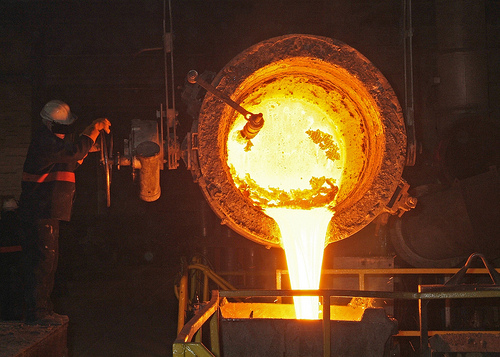 Understanding White Balance - a photograph showing molten metal being poured from a furnace. The metal is glowing yellow-white hot due to its heat