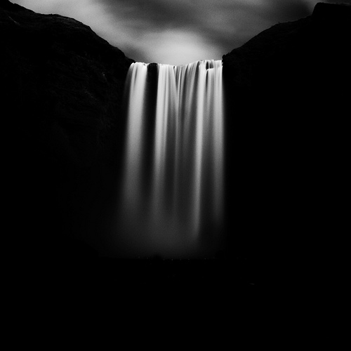 A black and white photograph of a waterfall. It's very dark and moody. The silky smooth water cascades from very high up. The water falls straight down over what looks like a great distance. It's a beautiful waterfall photograph.