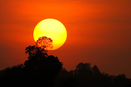A long telephoto lens was used to take this sunset photograph - this has compressed the perspective and make the sun look impressively large against the landscape's features.
