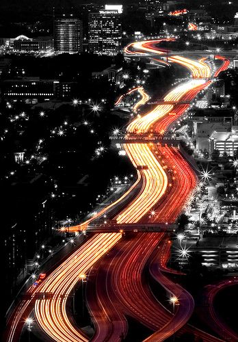 A shot of taillights flowing through a cityscape. It looks like a river of light. The photographer has added a black-and-white effect to the city scape meaning the only color is the light from the traffic