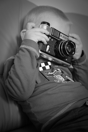 Cute black and white photograph of a young child holding an old camera