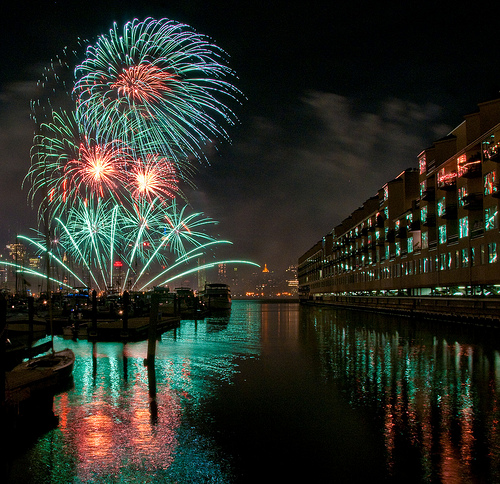 A beautifully exposed image of fireworks exploding in a night sky over water and commerical buildings. The balance between the exposure of the building and the exposure of the fireworks is near perfect.
