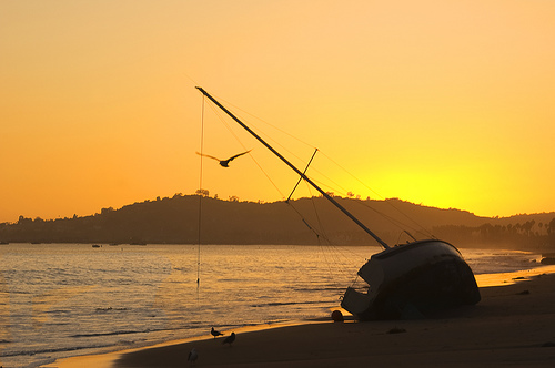 Silhouette of boat on the beach against a beautiful sunset - to illustrate this article on beach photography tips
