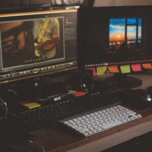 Two computer monitors, both with showing photographs being edited (probably using a program such as Adobe Photoshop)