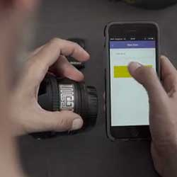 An RFID tag being attached to a camera lens to help prevent it getting lost as it can be scanned by the GearEye device